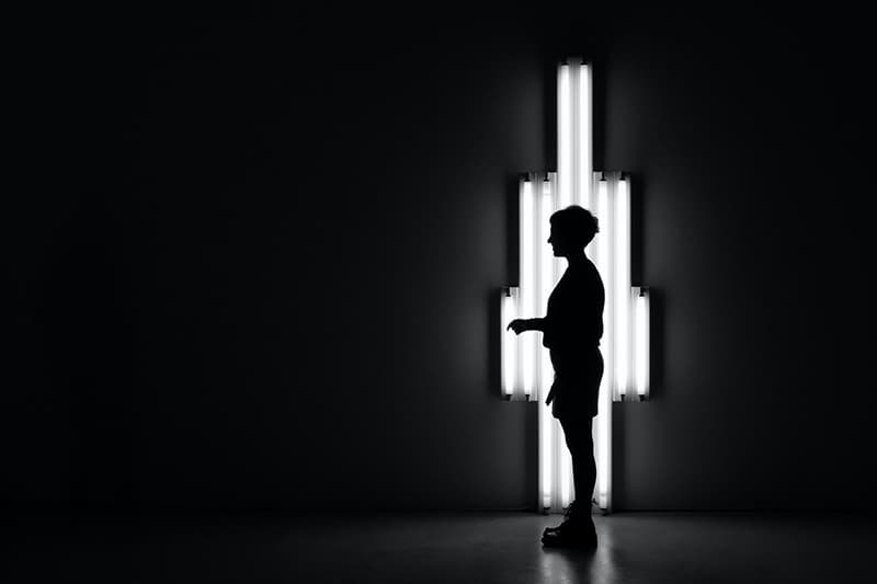 person standing in the dark in front of lamp