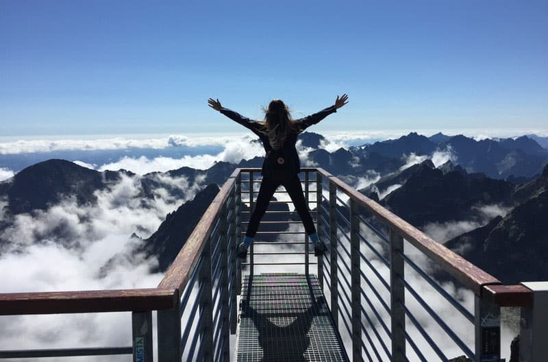 person standing on hand rails with arms raised facing the sea of clouds and mountains