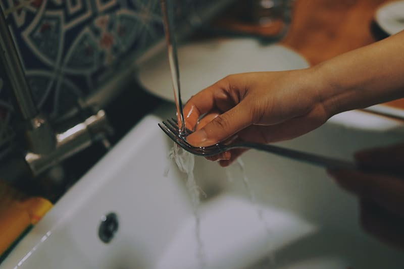 person washing the fork in a sink