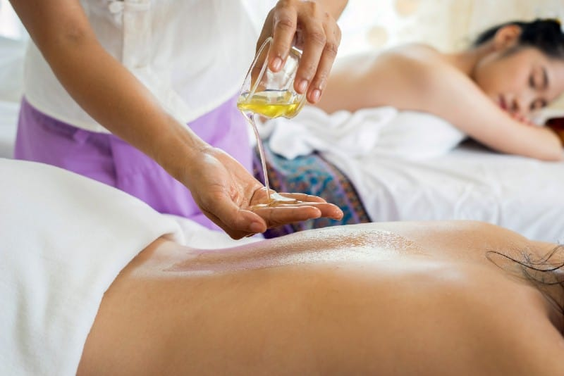 person pouring oil into hand before giving massage