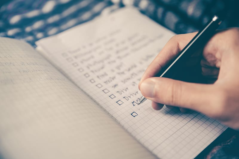 person writing bucket list on the notebook