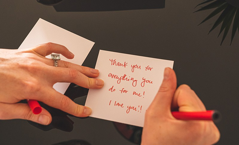 person writing note on white paper