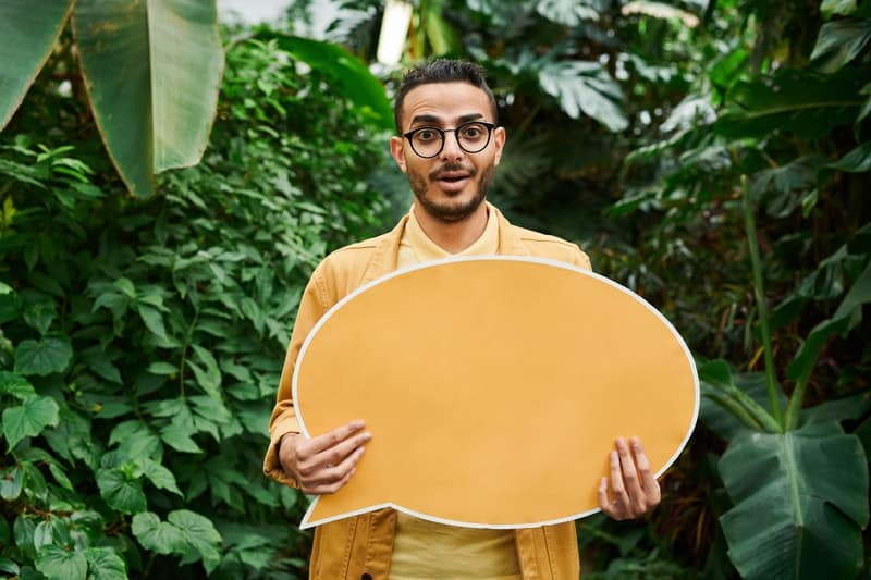 photo of a man holding a blank he said signage