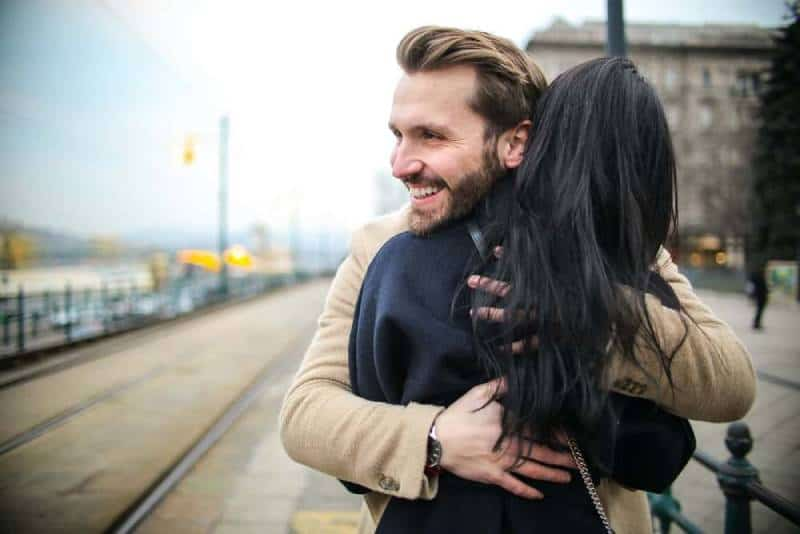 photo of man hugging woman