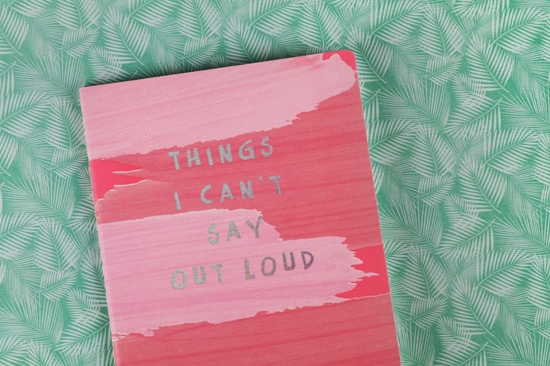 pink book on green table entitled things i cant say outloud