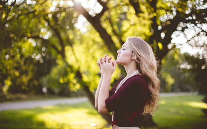 Praying young woman in a park during daytime