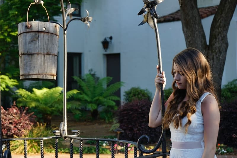 pretty woman in white dress standing the railings of the park near a well