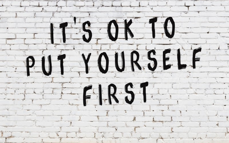 It's ok to put yourself first written on bricks wall