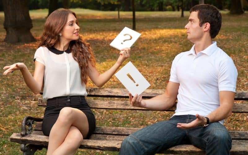 Quarrel between man and woman sitting on a bench in a park during daytime