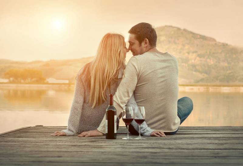 romantic couple sitting in front of lake on sunset