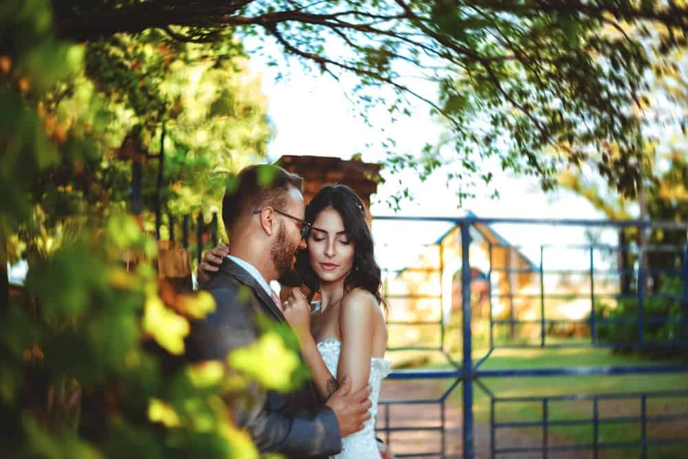 romantic couple standing near a gate