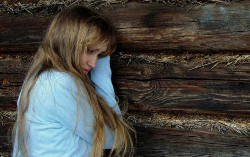 Sad blonde woman with long hair wearing blue top standing near wooden wall