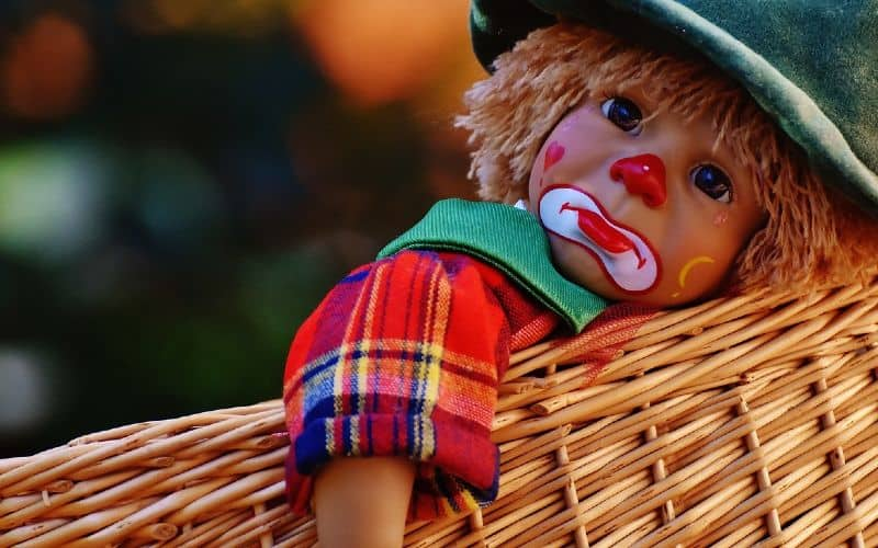 Sad clown doll in a basket
