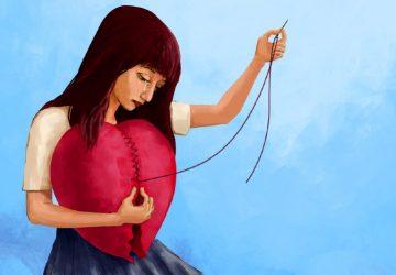 Sad wooman sewing a big red heart
