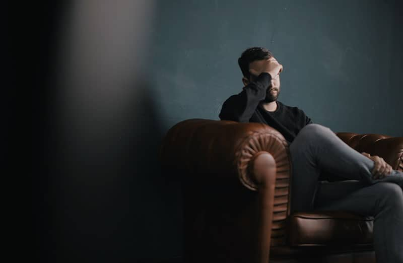 sad man in couch wearing dark top with hand on his forehead
