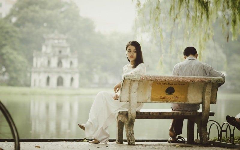 Sad woman and man sitting on a bench near a lake