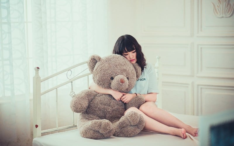 Sad woman holding big teddy bear while sitting on the bed
