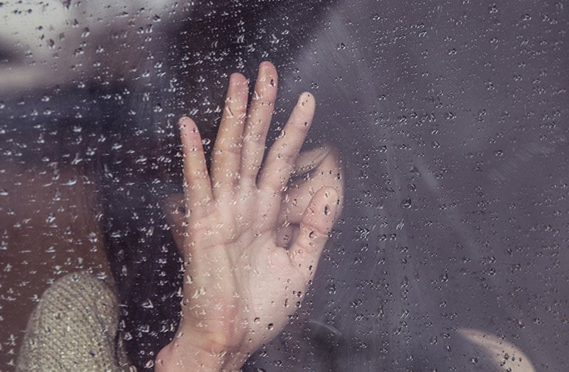 sad woman leaning on the glass hand covering her face