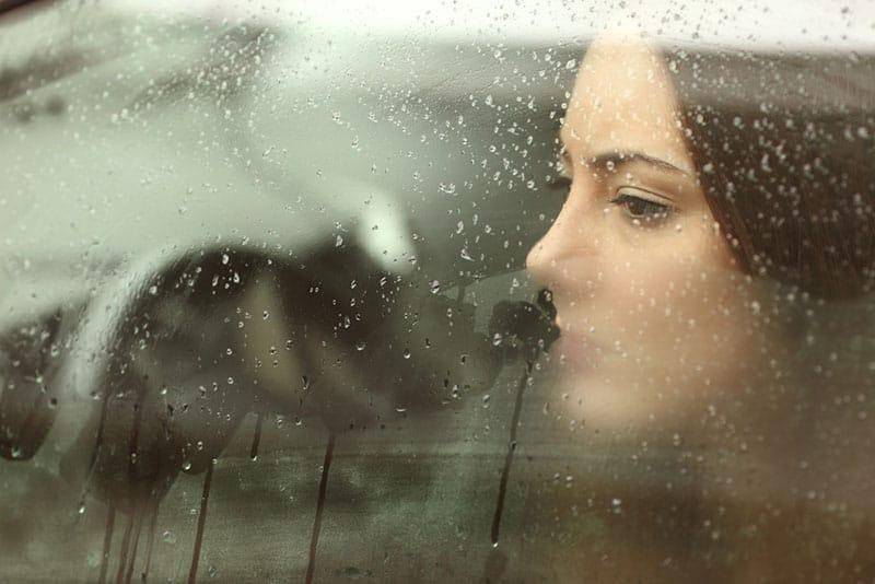 sad woman looking through rainy window