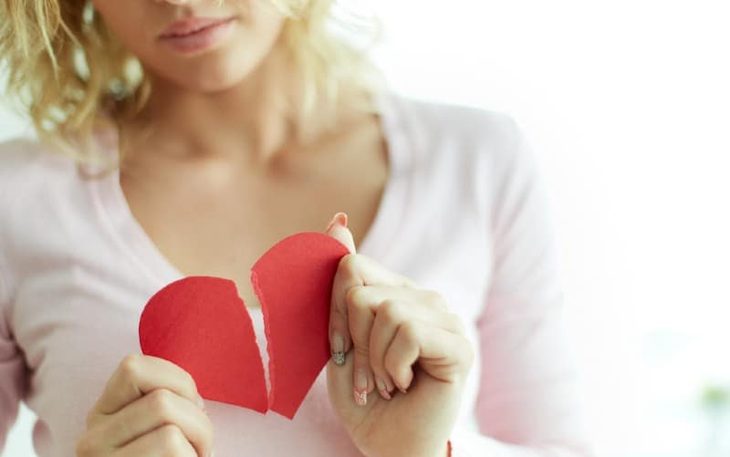 Close-up of sad woman showing red broken paper heart