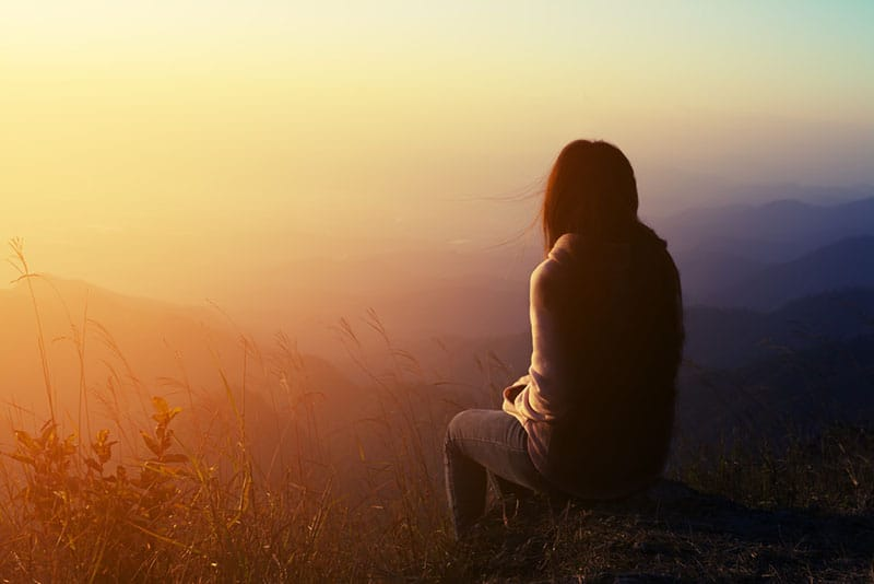 sad woman sitting on the top of mountain