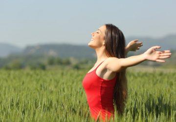 Happy woman wearing red dress on a green field