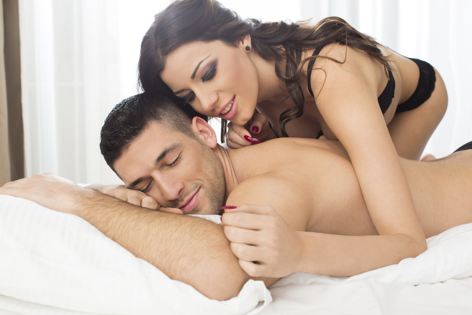 sexy woman in bed whispering on man's ear