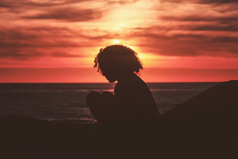 silhouette of girl sitting near sea during golden hour