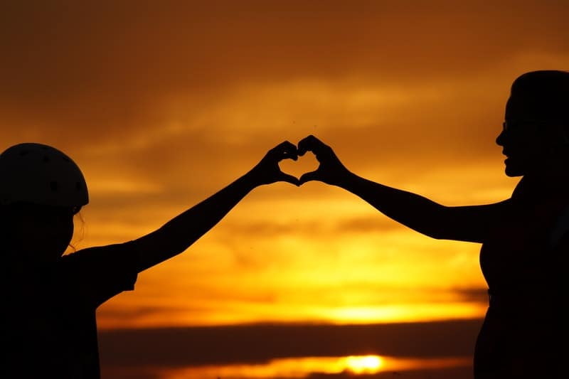 silhouette of man touching a woman in sunset forming heart shape