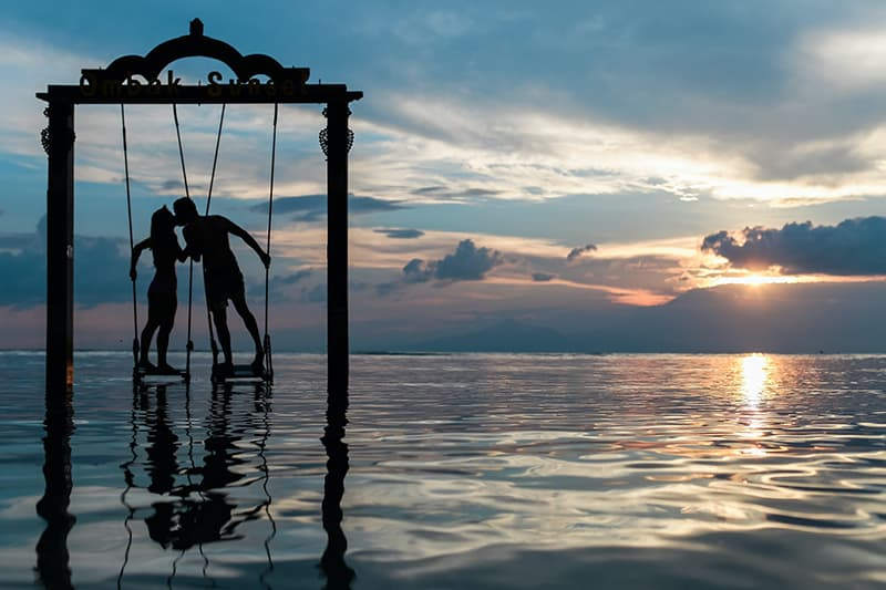 silhouette of kissing couple standing on swings under the sea