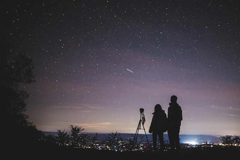 silhouette of two person standing during nightime