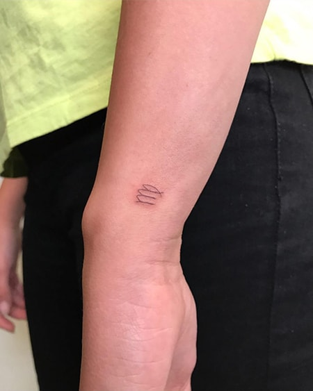 small Virgo symbol tattoo on the side of the wrist