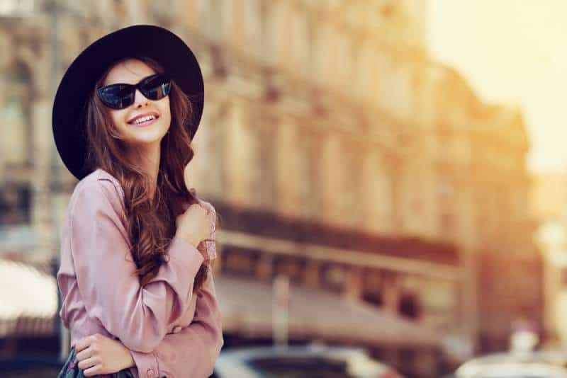 smilig woman wearing black hat and sunglasses