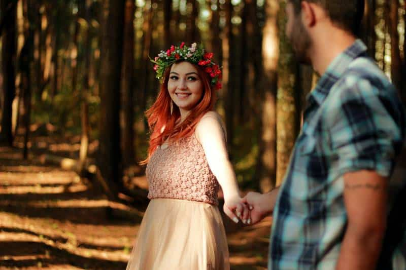 smiling couple holding their hands near trees