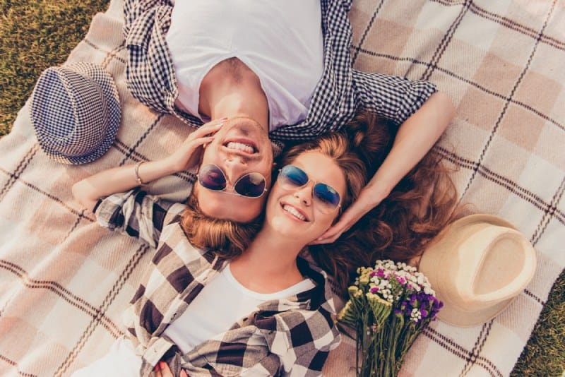 smiling couple lying on a blank outside in nature