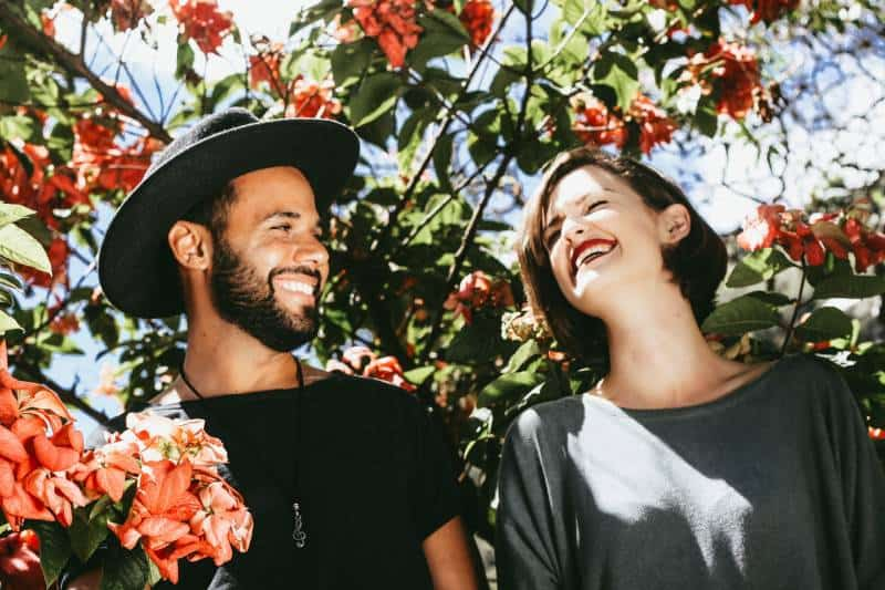 smiling couple surround by the flowers