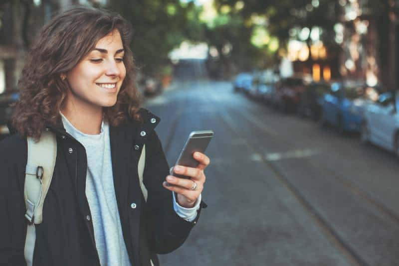 smiling girl typing on her phone outside