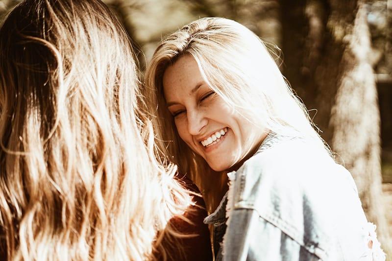 smiling girl with blonde hair wearing blue denim jacket