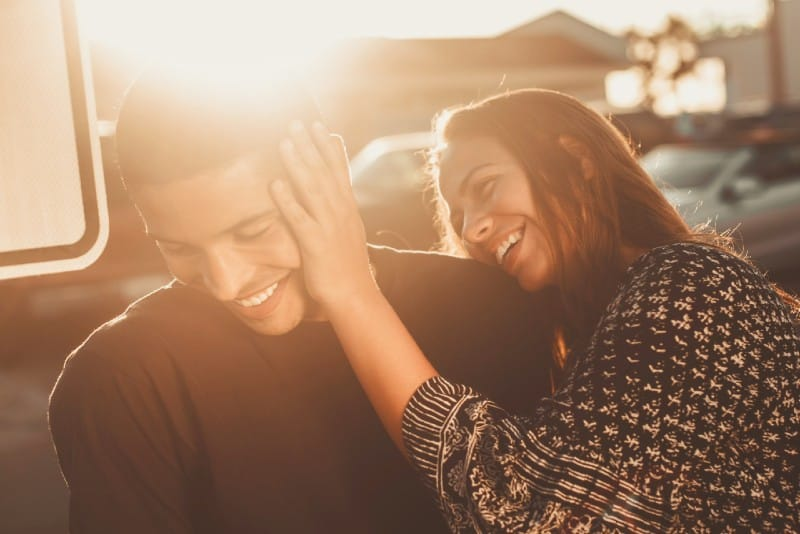 smiling woman touching man's face outdoor
