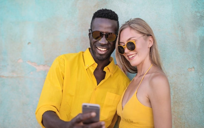 Smiling man in yellow shirt standing beside smiling woman looking at a phone