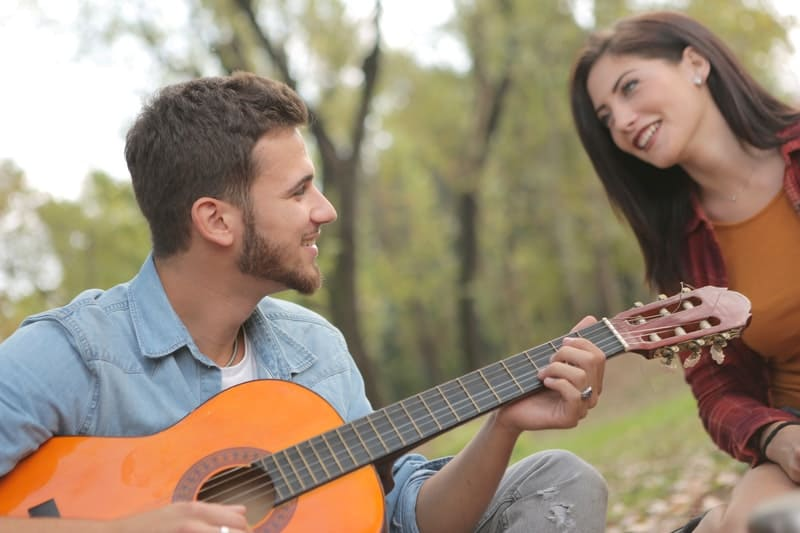smiling man playing guitar beside a happy woman in the park