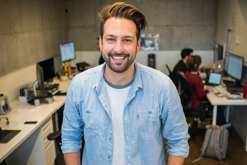 smiling man wearing blue shirt while standing inside the room