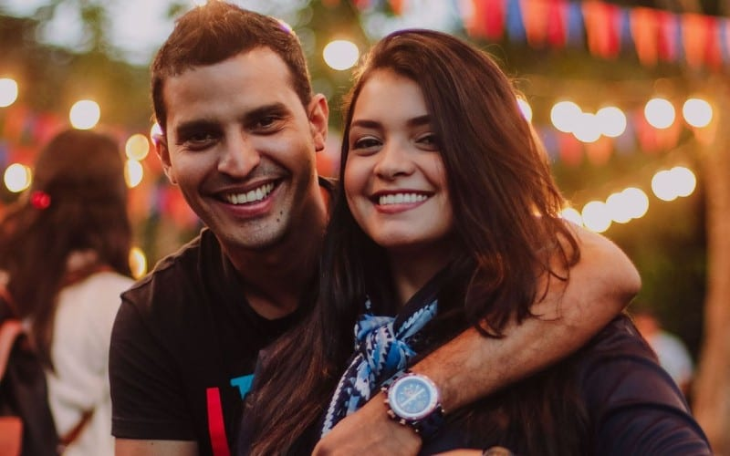smiling man with hand around woman head