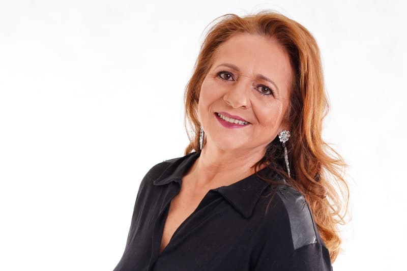smiling red haired woman wearing silver colored stud earrings and black collared top