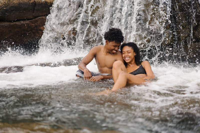 smiling topless man sitting near his girlfriend near waterfall