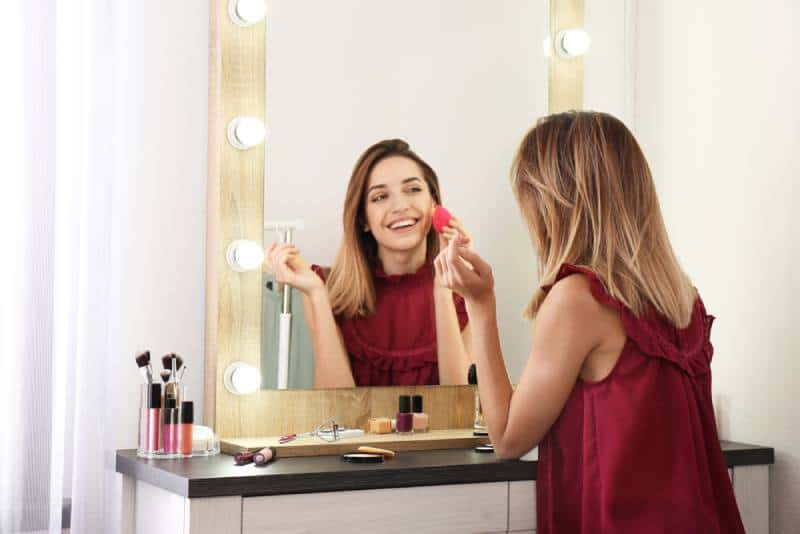 smiling woman applying makeup in front of mirror