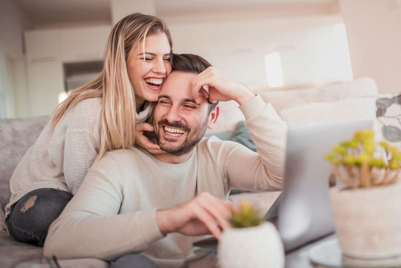 smiling woman hugging a man in the living room