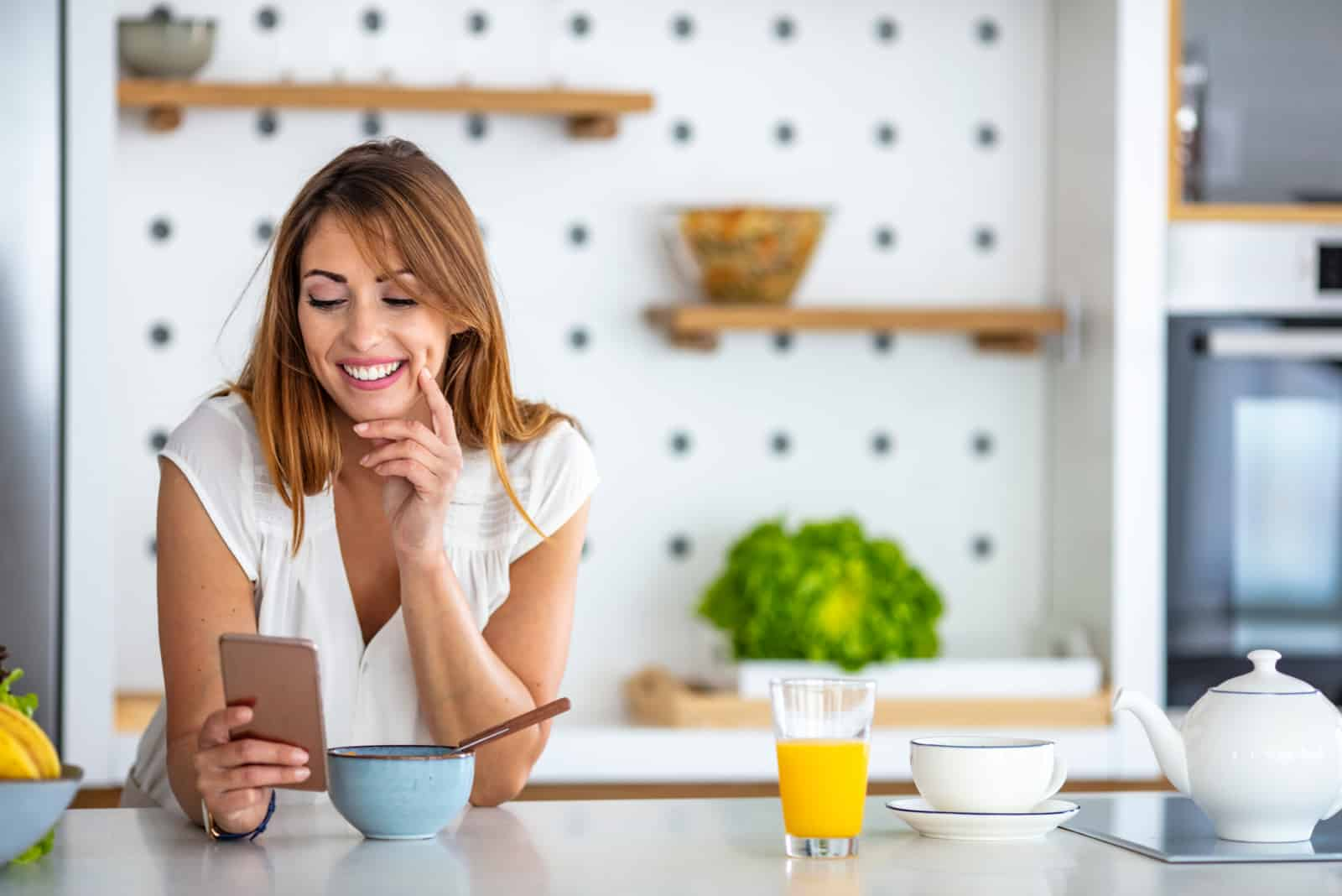 smiling woman in the kitchen button on the phone
