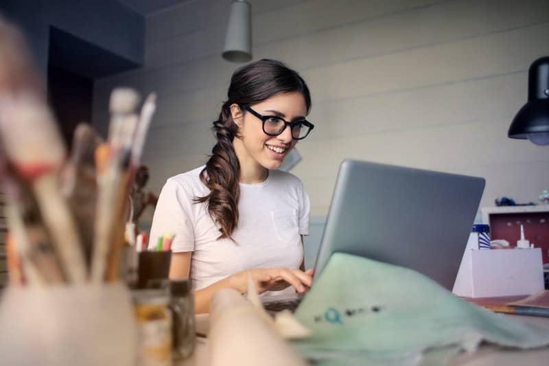 smiling woman using her laptop wearing eyeglasses and white shirt