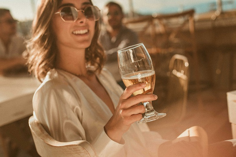 smiling woman wearing sunglasses while holding glass of wine